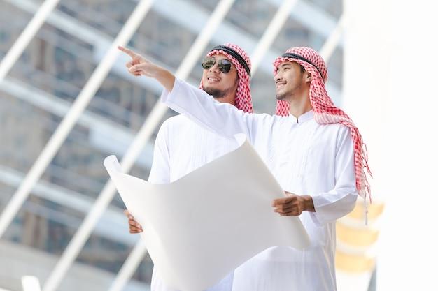 Арабский деловой человек, глядя на план плана в городе