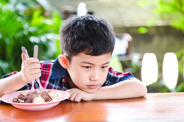 アジアの小さな男の子は木製のテーブルの上に米の食べ物を食べて退屈