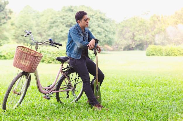 自転車に乗っている肖像画のアジアの若い男性ギター