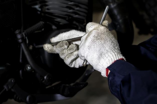画像がクローズアップされ、人々はオートバイを修理していますレンチとドライバーを使用して作業してください。