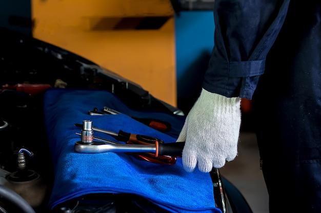 整備士はレンチを拾ってエンジン内の車を修理しようとしています。