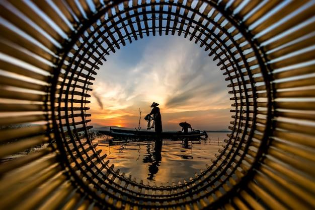 漁師のキャスティングは、早朝から木製ボートで釣りに出かけています。