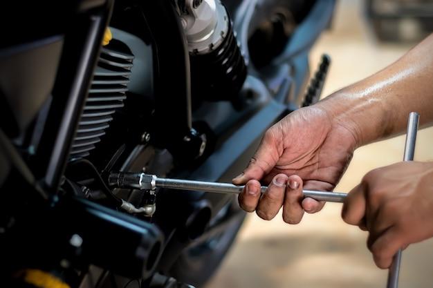 人々はオートバイを修理しています仕事にはレンチとドライバーを使ってください。