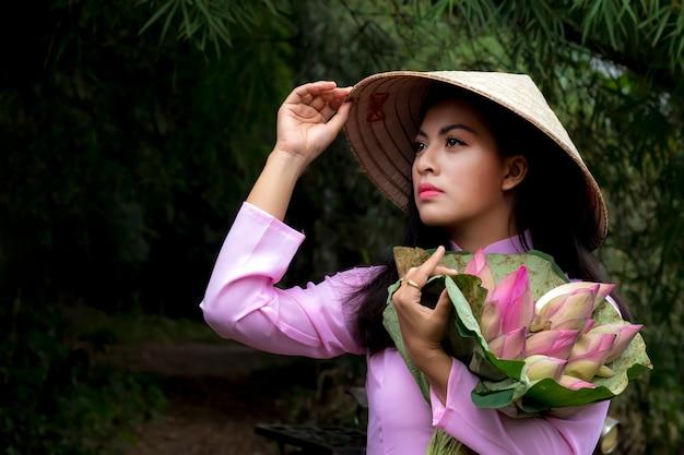 蓮の花のバスケットと伝統的なアジアの女性。