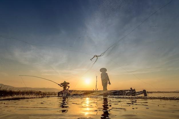 漁師のキャスティングは、早朝に木製のボートで釣りに出かけています