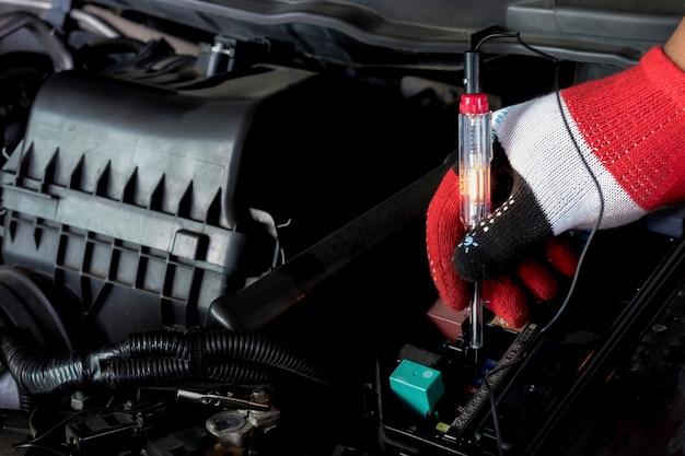 エンジンルームのドライバーチェックヒューズ。プロの整備士がドライバーを使用しています。
