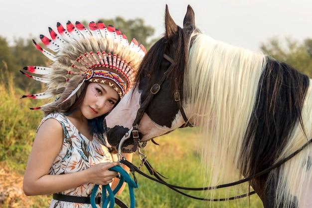 若くてきれいな女性、美しさ、民族部族のメイク、顔、赤い唇、イヤリング、ボヘミアンヒッピースタイルと馬の絵。