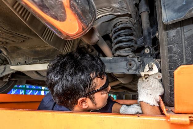 男性はドライバーと車の修理レンチ車の衝撃吸収材を使用しています。