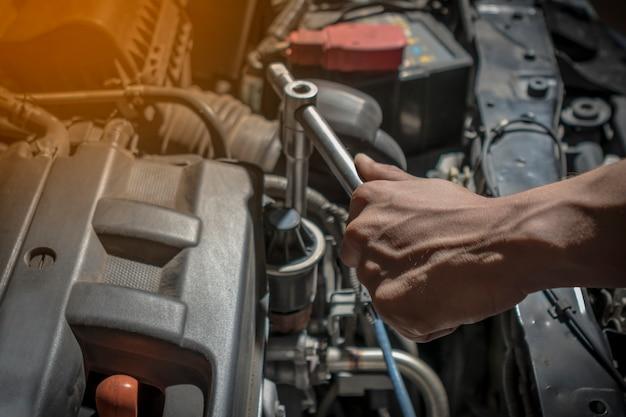 車を修理しています。作業にはレンチとドライバーを使用してください。