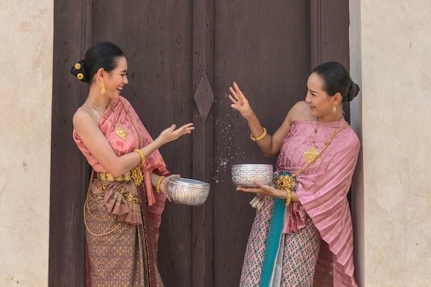 タイの文化タイの女の子とタイの女性がアユタヤタイ祭ソンクラーン祭りの寺院でタイの伝統的な衣装の中に水しぶきをして遊んで。