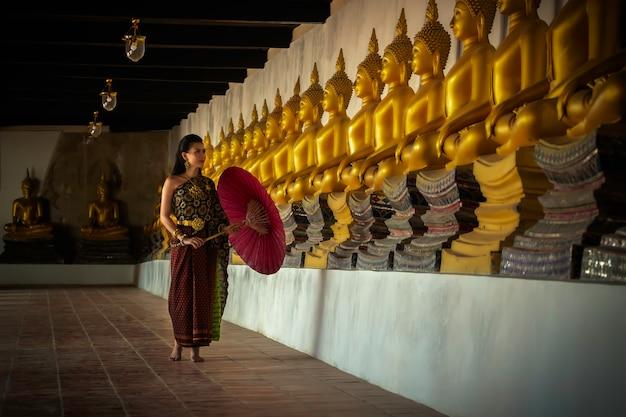 美しい女性タイの女の子寺院アユタヤ、タイのアイデンティティ文化の伝統的なタイ衣装で手蓮を保持しています。