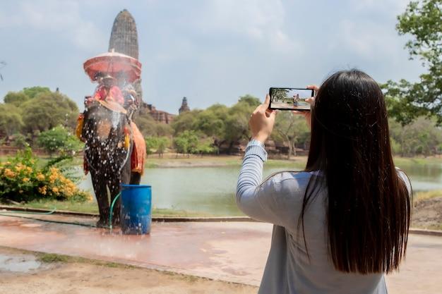 旅行女性は寺院アユタヤで象の写真を撮る