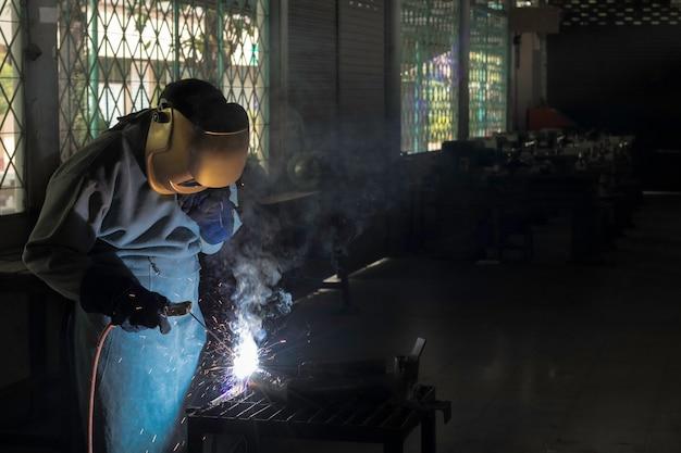 Ремесленник сваривает сталью заготовки. рабочий о сварщике стали использование электросварочного аппарата в фабричной промышленности выходят линии света и оборудование для обеспечения безопасности.