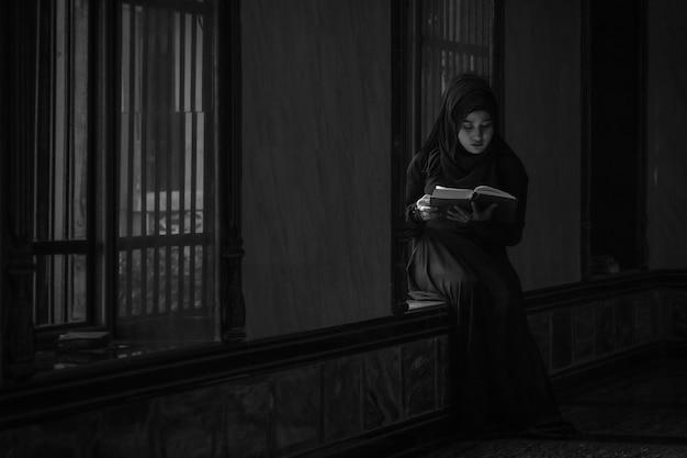 画像は白黒です。黒いシャツを着ているイスラム教徒の女性イスラム教の原則に従って祈りをしています。