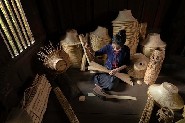 若い女性はタイのフィールド手作りバスケットで織っています。