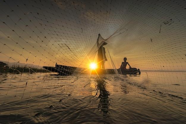 画像はシルエットです。漁師のキャスティングは、早朝から木製のボート、古い提灯、網で釣りに出かけています。コンセプト漁師のライフスタイル。