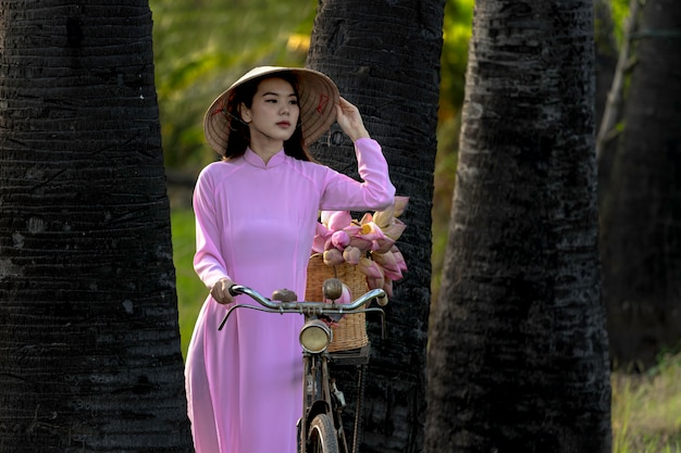 アジアのかわいい女の子ベトナムアオザイの伝統的な衣装を着てベトナムのピンクのドレス。アジアの女性ベトナムは蓮の花のバスケットの後に店に女の子のトロリーバイクです