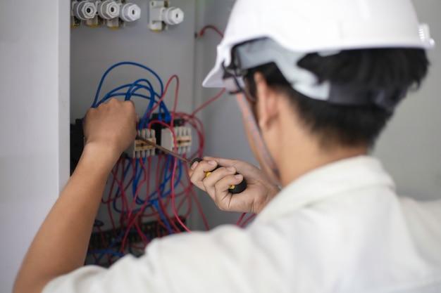 電気技師は安全ヘルメットの前の電気技師の作業を保持しています。