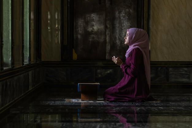 イスラムの祈りをしている紫色のシャツを着ているイスラム教徒の女性。