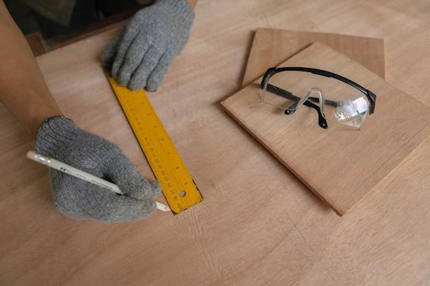 Плотник работает на деревообрабатывающих станках в столярной мастерской. опытный плотник режет кусок дерева в своей мастерской.