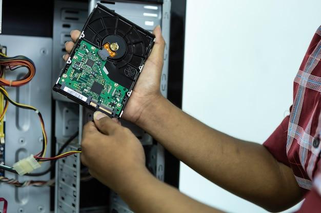 アジア人男性コンピューター技術者ドライバーコンピューターマザーボード修理安全装置は眼鏡です。コンピューターによるサービス。