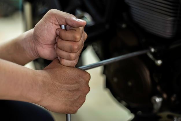 画像はクローズアップ、自動メカニックはオートバイを修理していますレンチとドライバーを使用して作業します。