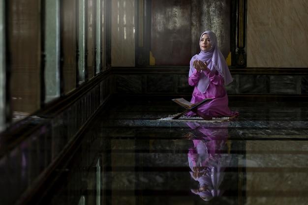 イスラム教の原則によると、紫色のシャツを着たイスラム教徒の女性が祈りをしています。
