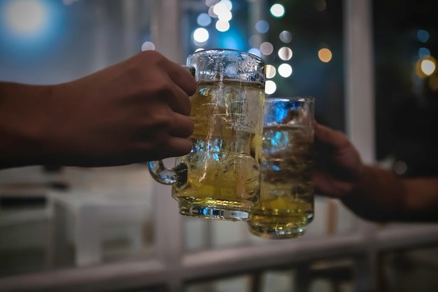 Два друга тостов с бокалами светлого пива в пабе
