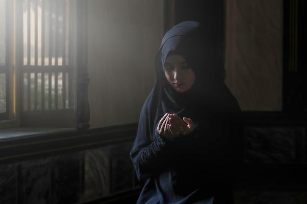 イスラム教の原則によると、黒いシャツを着たイスラム教徒の女性が祈りをしています。