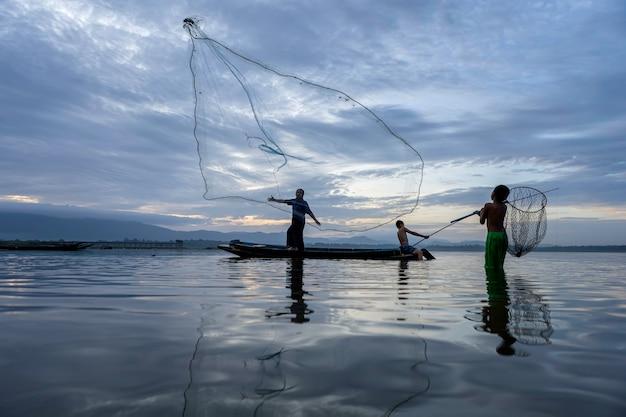画像はシルエットです。漁師キャスティングは、木製ボート、古いランタン、ネットで早朝に釣りに出かけます。コンセプトフィッシャーマンズライフスタイル