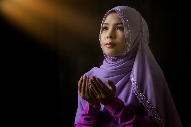 閉じる。イスラム教の原理によると、紫色のシャツを着たイスラム教徒の女性が祈りをしています。