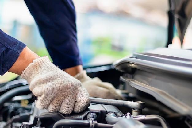 Закройте вверх, азиатский автоматический механик человека используя ключ и отвертку к работая служебному автомобилю в гараже.