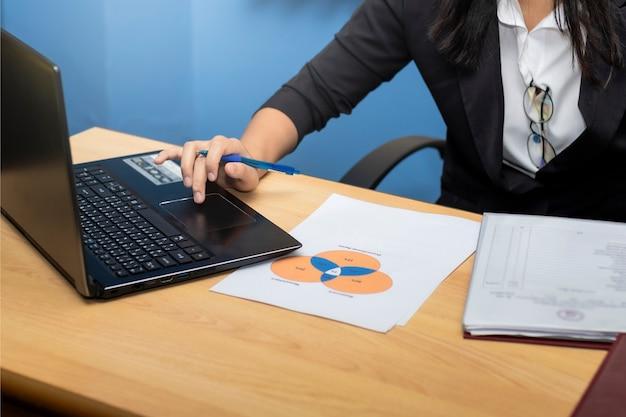 閉じる。ビジネスの女性は、コンピューターノートラップトップを使用して、グラフで手書きと紙の書き込みを使用します。