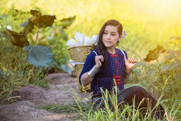 ロータスの伝統的な衣装で農家タイ文化に座っているアジアの女性。
