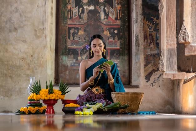 ロイクラトン祭りタイ。夜の川でロイクラトンのクラトンを保持しているアジアの女性。
