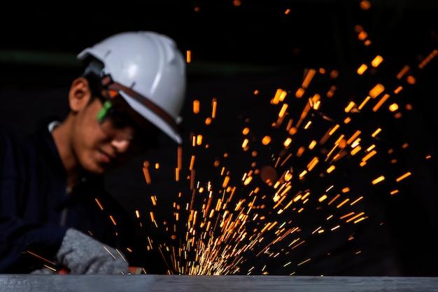 Ремесленник сваривает сталью заготовки. рабочий человек о сварщике стали использование электросварочного аппарата в фабричной промышленности выходят линии света и оборудование для обеспечения безопасности.