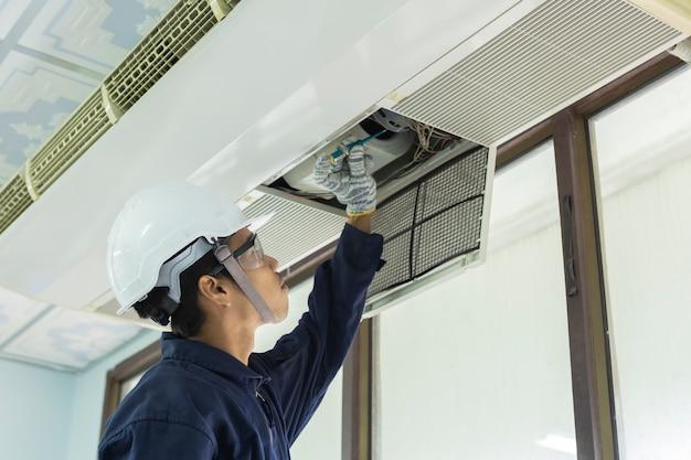 エアコンの清掃。手袋の男はフィルターをチェックします。若い男が空調システムを調整します。