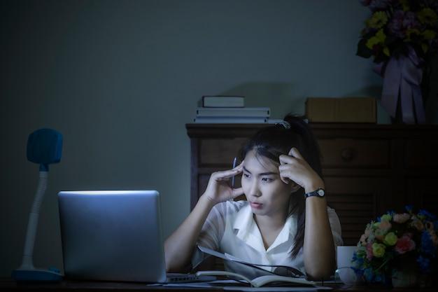 Утомленная унылая перегруженная азиатская бизнес-леди чувствуя усталость, головную боль пока работающ поздно ночью дома.
