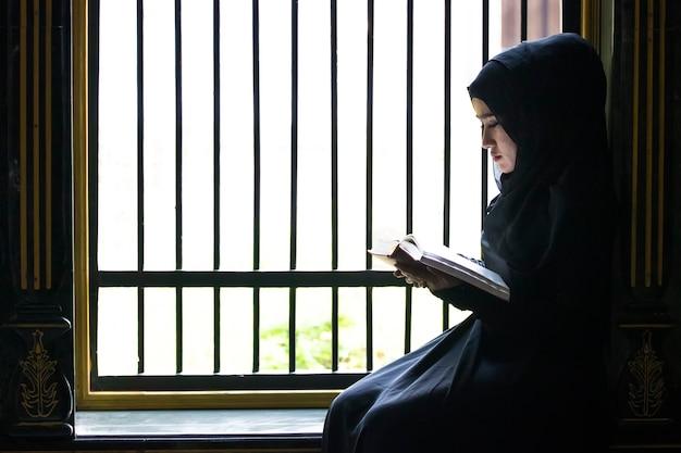 イスラム教徒の少女が黒い頭のスカーフを入れてイスラム教のテキストを読んでいた。厳密に