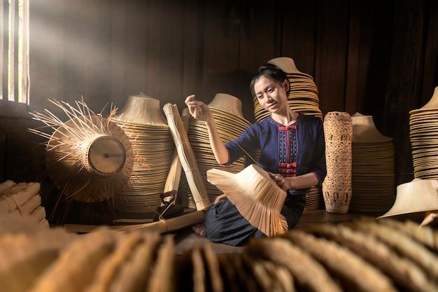 若い女性は、タイのフィールド手作りバスケットに織り込んでいます。