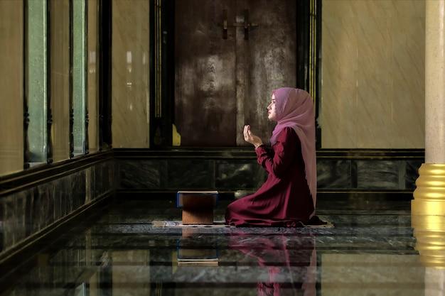 赤いシャツを着たイスラム教徒の女性イスラム教の原則によると祈りをしています。
