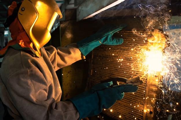 Ремесленник сваривает заготовку из стали.