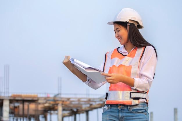 Архитектор здания плана бумаги инженера-строителя азиатской женщины нося белый шлем безопасности