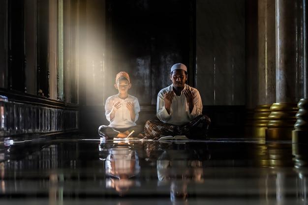 イスラム教徒の子供子供と老人が白いシャツを着て教える本を読んで祈りをやって