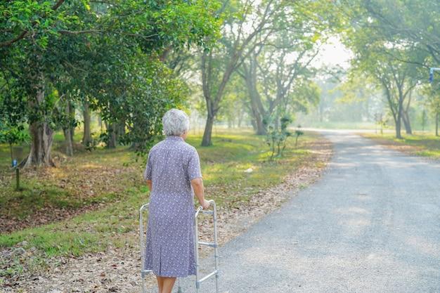 年配の女性は公園でウォーカーと歩きます。