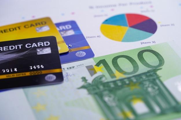 グラフグラフの背景にユーロ紙幣とクレジットカード。