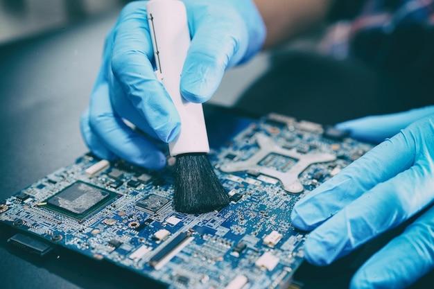 アジアの技術者が汚れやほこりのマイクロ回路のメインボードコンピューティングを修理およびクリーニングします。