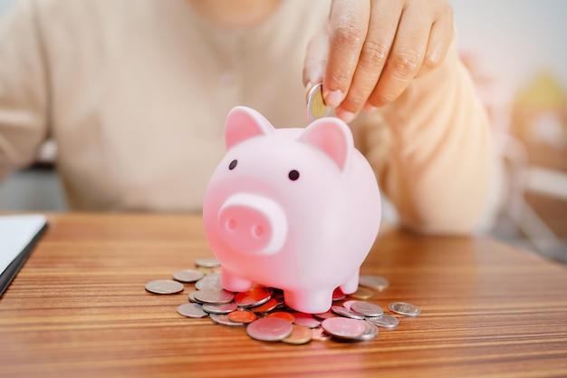 お金を節約、ピンクの貯金箱にコインを入れる:金融の概念。