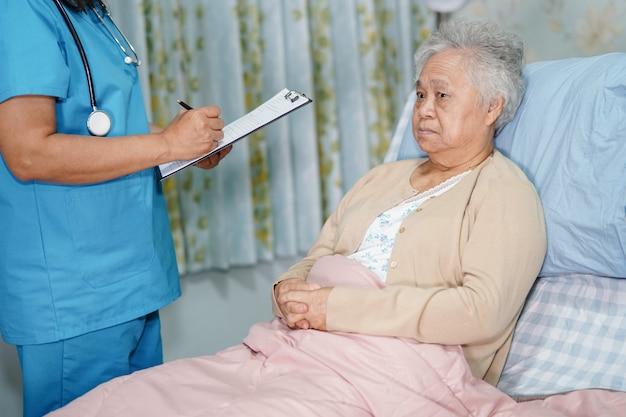 病院でアジアの年配の女性と診断とクリップボード上のメモについて話している医者。