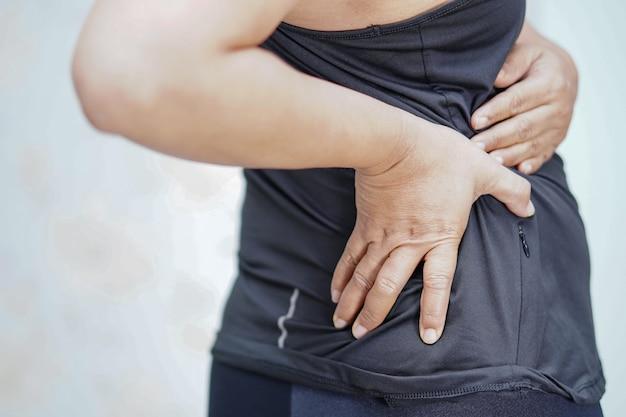 アジアの中年女性は背中に触れて痛みを感じます。